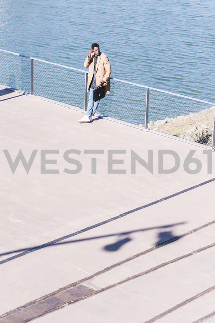 Businessman standing at the riverside with briefcase and earphones - UUF13136