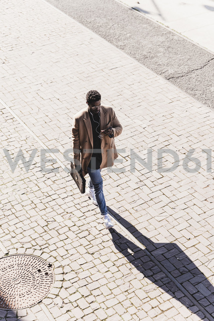 Businessman walking outdoors with briefcase, cell phone and earphones - UUF13139