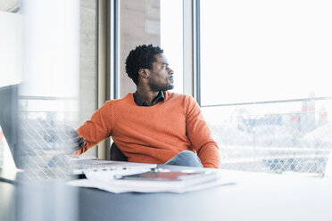 Casual businessman sitting at desk looking out of window - UUF13148