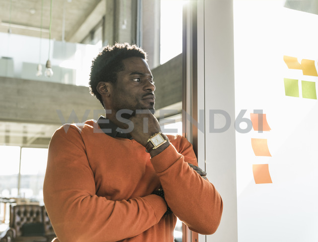 Casual businessman in office at wall with adhesive notes - UUF13151