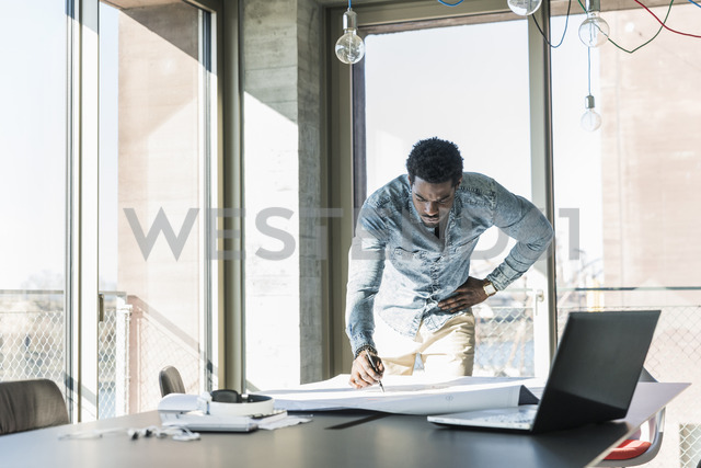 Casual businessman working on plan at table in office - UUF13160