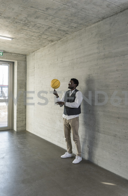 Businessman balancing basketball on office floor - UUF13169