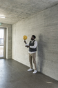 Businessman balancing basketball on office floor - UUF13169