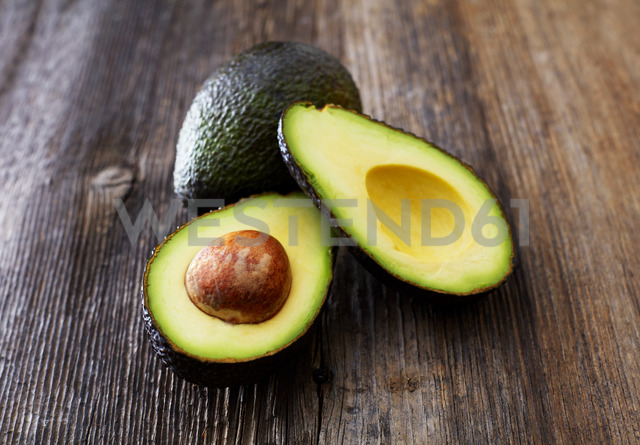 Whole and sliced avocado on wood - KSWF01830