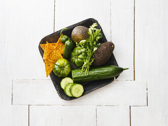 Wooden bowl of avocados, green tomatoes, Jalapeno peppers, cucumber and tortilla chips - KSWF01842