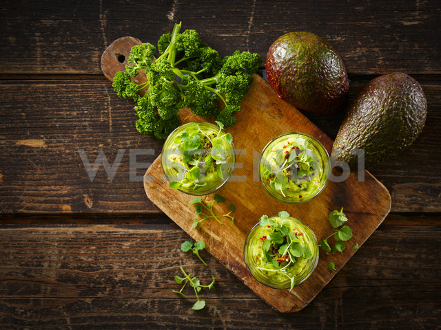 Glasses of avocado cream with chili flakes, cress and parsley - KSWF01848