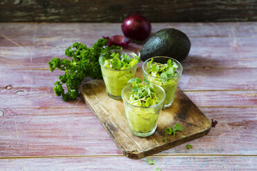 Glasses of avocado cream with chili flakes, cress and parsley - KSWF01860