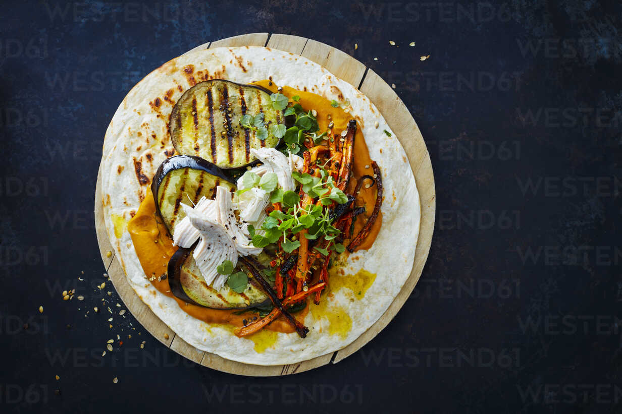 Pulled Chicken Wrap, carrot, grilled aubergine, curry hummus and herbs on chopping board - KSWF01866 - Kai Schwabe/Westend61