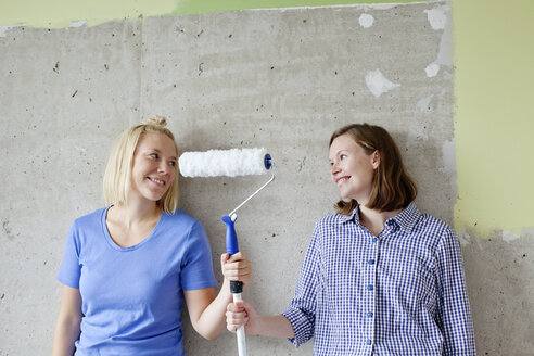 Young women standing by wall and holding paint roller - FOLF00035
