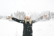 Smiling woman with falling snow in foreground - FOLF00113