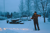 Young man holding Christmas lights in backyard at dusk - FOLF00116