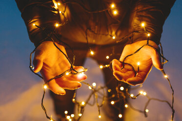 Young man holding Christmas lights - FOLF00119