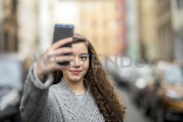 Teenage girl taking smartphone selfie in the street - FMKF04982