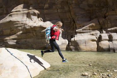 Female backpacker jumping in water on sunny day - CAVF28385