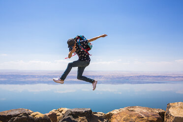 Happy woman jumping on mountain against sea - CAVF28388