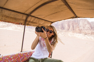 Happy woman in sunglasses photographing while traveling in vehicle - CAVF28391