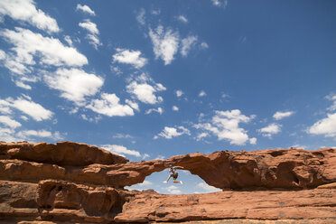 Woman jumping on rock formation against sky - CAVF28394