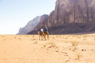 Friends riding on camel in desert against clear sky - CAVF28397