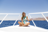 Happy woman sitting on boat against clear sky - CAVF28400