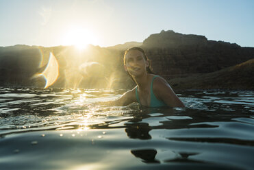 Woman swimming in sea against mountain during sunset - CAVF28403