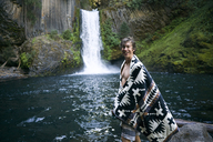 Portrait of happy man in shawl standing by waterfall in forest - CAVF28430