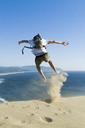 Rear view of playful man jumping on sand at beach against clear blue sky - CAVF28433