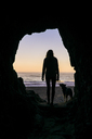 Silhouette woman with dog standing at cave entrance against beach - CAVF28442