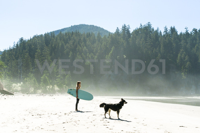 Woman holding surfboard with dog standing at cannon beach - CAVF28445 - Cavan Images/Westend61