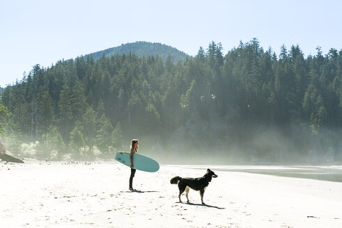 Woman holding surfboard with dog standing at cannon beach - CAVF28445