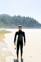 Portrait of happy man holding surfboard while standing at beach - CAVF28451