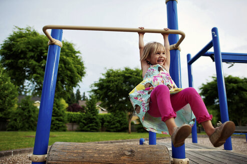 Cheerful girl hanging on monkey bars in park - CAVF28499