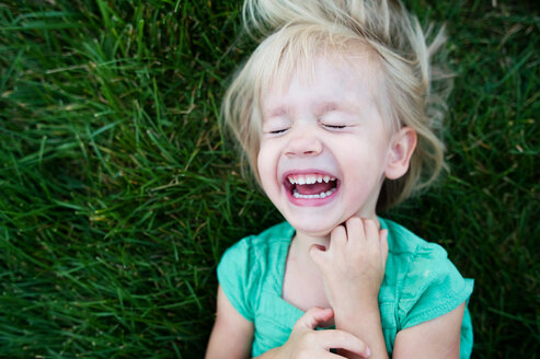 Overhead view of girl crying while lying on grassy field at park - CAVF28523