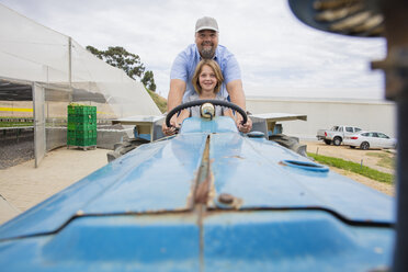 Farmer showing his daughter, how to drive a tractor - ZEF15227