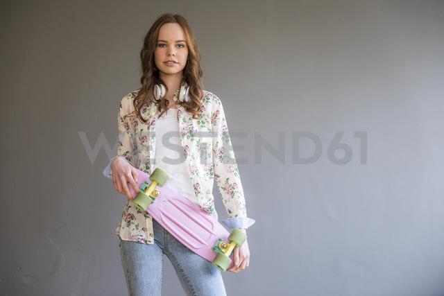 Portrait of teenage girl with pink skateboard - FMKF04989