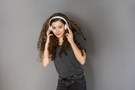 Portrait of teenage girl with curly hair listening music with headphones - FMKF05013