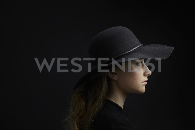 Profile of sad young woman wearing black hat against black background - PDF01558