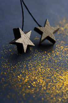 Wooden stars on dark background with golden glitter - HSTF00060