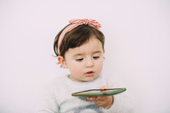 Portrait of baby girl looking at cell phone - GEMF01906