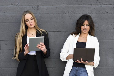 Two businesswomen using tablet and laptop - JSMF00136