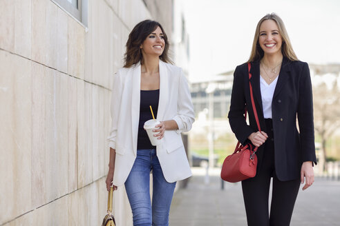 Portrait of two happy businesswomen with handbags and coffee to go walking on pavement - JSMF00139