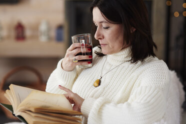 Mature woman with a hot drink reading a book - ABIF00189