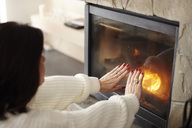 Mature woman warming her hands at the fireplace - ABIF00192