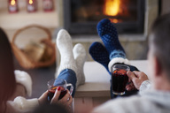 Mature couple with hot drinks in living room at the fireplace - ABIF00195