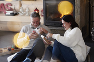Happy mature couple at the fireplace unpacking gifts - ABIF00198