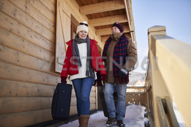 Mature couple with suitcases walking at mountain hut in winter - ABIF00201