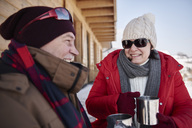 Happy mature couple with hot drinks outdoors at mountain hut  in winter - ABIF00204