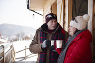 Mature couple with hot drinks talking outdoors at mountain hut  in winter - ABIF00207
