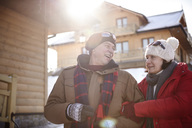 Happy mature couple in mountain village in winter - ABIF00210