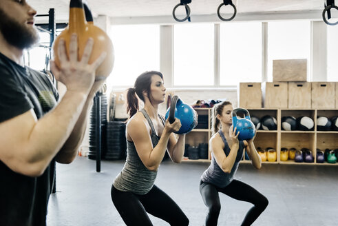 Young women and man cross training with kettlebells in gym - FOLF00406