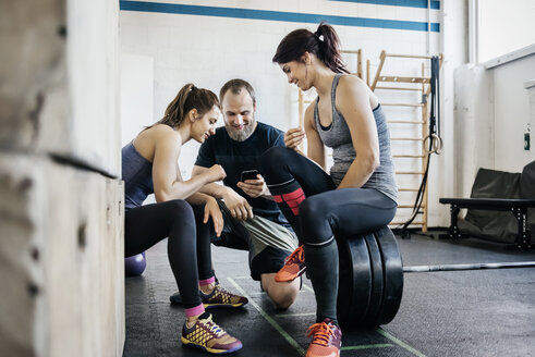 Young women and man looking at phone in gym - FOLF00412